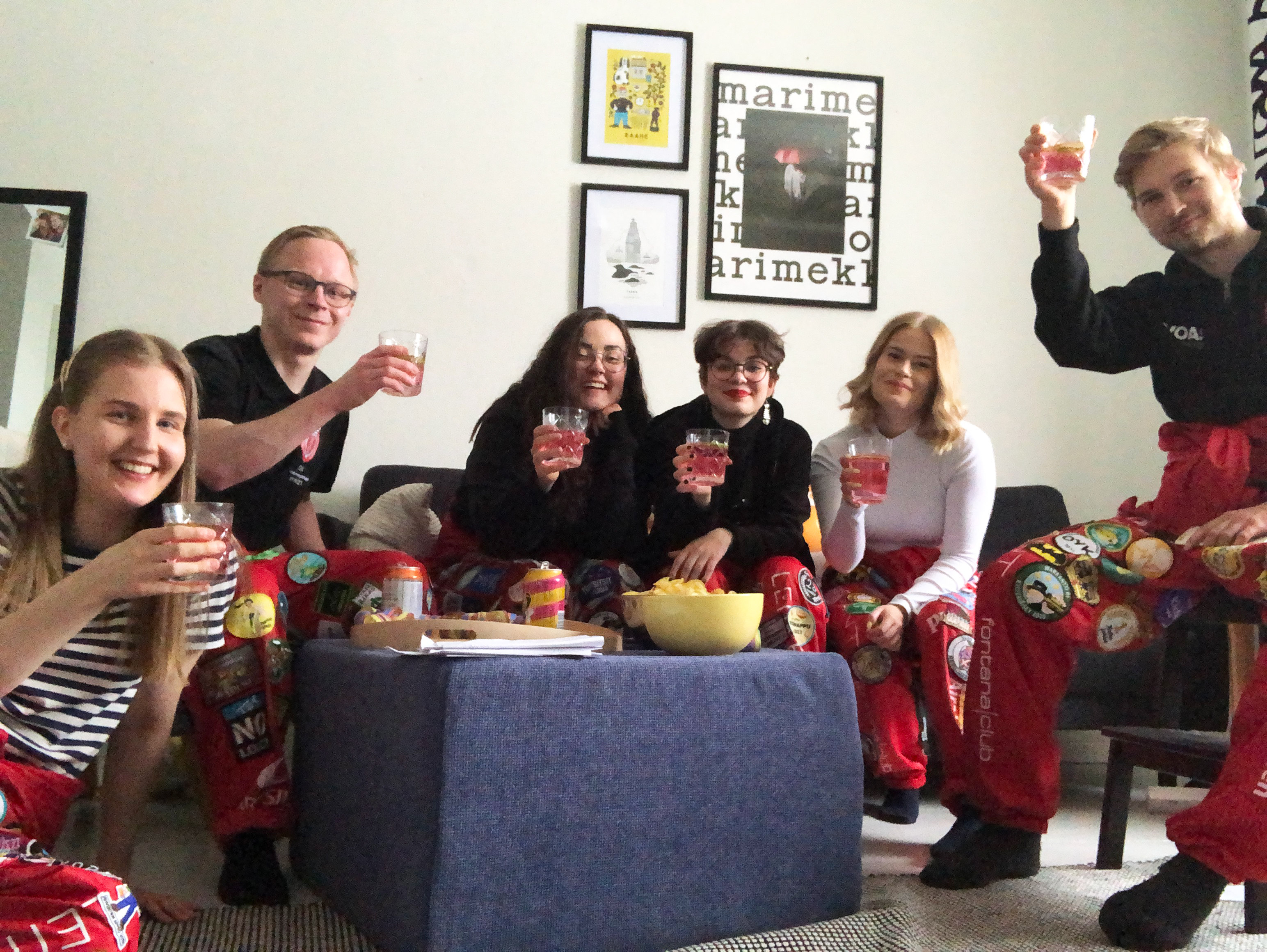 Six happy students wearing overalls cheersing to the camera