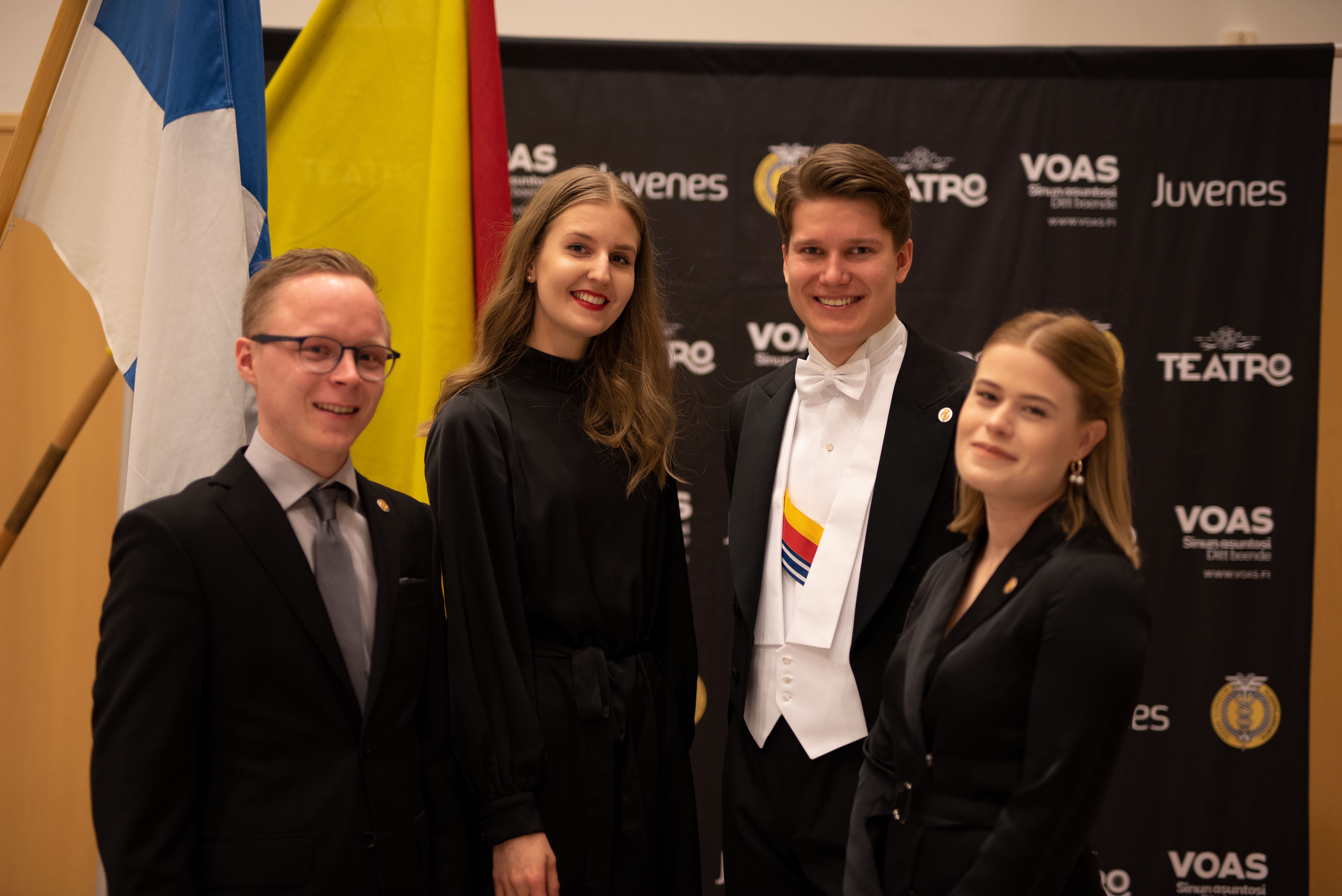 Board's Olli, Sara, Henri and Aada standing in front of Finland's and the Student Union's flags during the annual celebrations