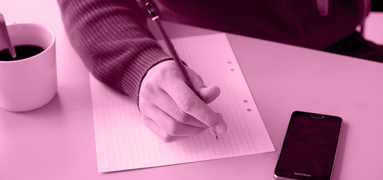 Opiskelija kirjoittamassa ruutupaperille lyijykynällä