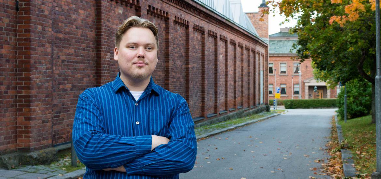 Aleksi Sandroos seisoo Vaasan yliopiston kampuksella tiiliseinän edessä