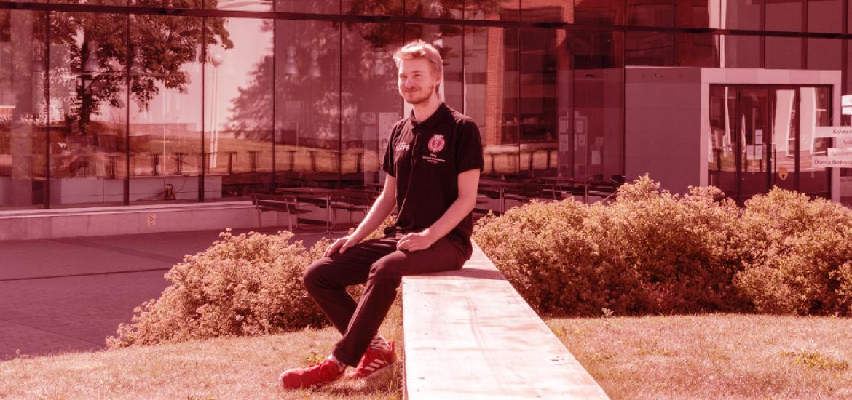 Elmo Nikula istuu pitkän metallisen penkin päädyssä hymyillen.