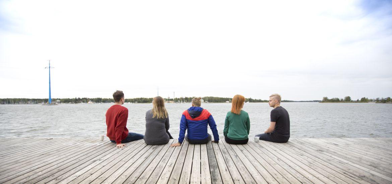 Viisi henkilöä istuu laiturilla ja katsoo merelle
