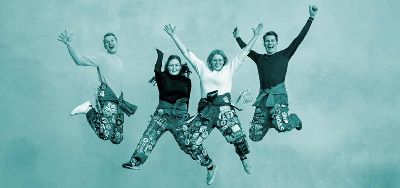 Neljä opiskelijaa opiskelijahaalareissa hyppää iloisesti